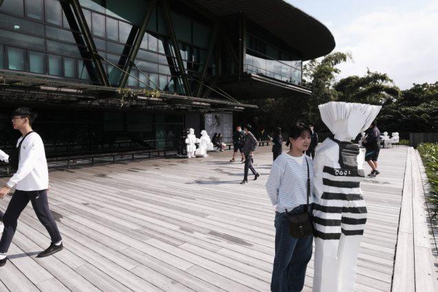 彫刻と一緒に淡水街並みをの眺める真優さん。