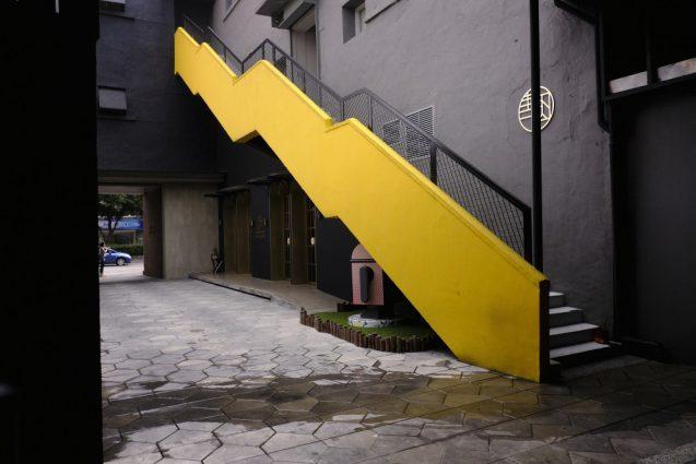 CAFE&BAR MACHI34前のパティオ。鮮やかなイエローの階段。ちなみにこの後ろに入院中?のバオビーくんが3匹いました。笑