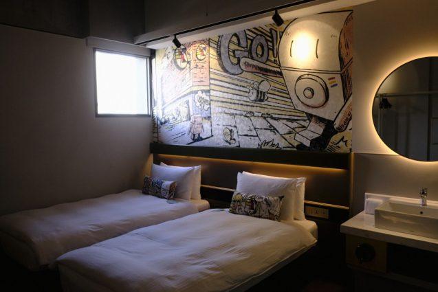 客室内ベッド側の全景。ベッドボード上のイラストレーション。バオビーくんのコンセプトイラストとのこと。